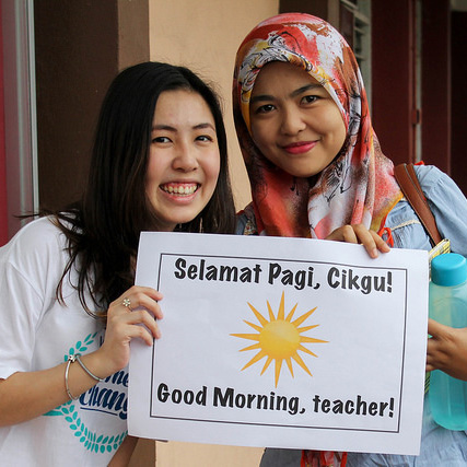 Facilitator and teacher holding a good morning sign