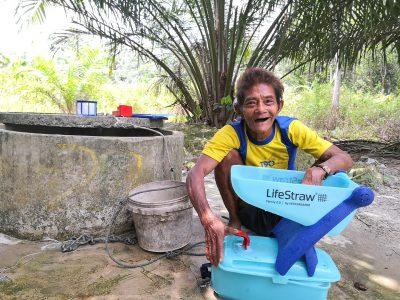 An orang asli washing the Lifestraw filter